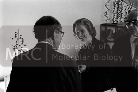 Margaret Thatcher talks to Max Perutz, in the LMB Model Room, during a private visit to LMB on 27 August 1980, as her husband, Denis, looks on.