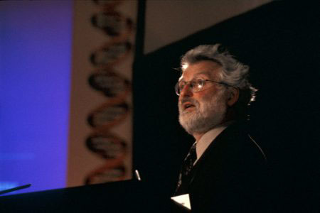 John Sulston on stage at the 'DNA:50 Years of the Double Helix' conference , Lady Mitchell Hall, Cambridge, 25 April 2003.
