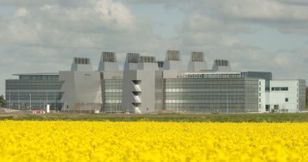 Exterior view of LMB building from south-east, across field of rape seed oil