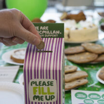 Donation being added to Macmillan collection box